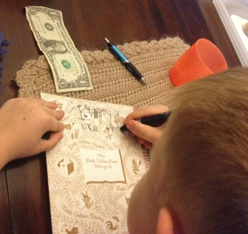 My 6-year-old writing a note inside a book to donate to The Nobelity Project's 1000 Books for Hope project. The dollar was to be placed inside to help offset shipping costs.