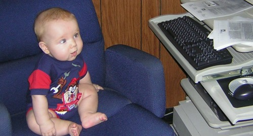 My son at six months, trying out the boss's chair at the family business.