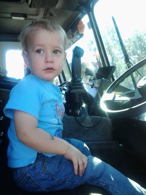 Catherine's son sitting in a trash truck at the 2013 event- a dream come true for the tot!