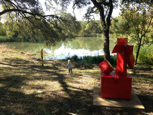"The red sculpture is ""Inspired World"" by Brother Mel Meyer and the smaller sculpture to the left is ""Peace Pole"" created by Summer Camp 2014 students."