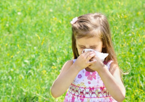 girl-sneezing-in-field