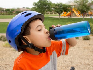 Young boy taking a break from riding his bike to rehydrate